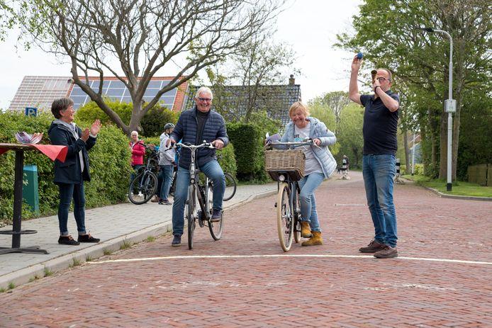 Hans van den Assem (rechts) geeft om de twee minuten een startssein met de toeter om de deelnemers aan de fietstocht vanuit Noordwelle in duo's te laten vertrekken. Marianne de Jonge (links) houdt het schema bij en moedigt de deelnemers, zoals Arie en Marlies Deurloo, aan bij de startstreep.