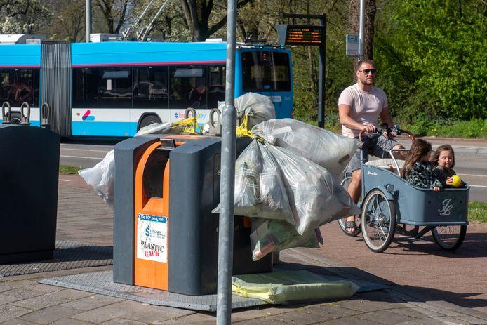 Overvolle containers bij winkelcentrum Elderhof in de Arnhemse wijk Elderveld. Hier is juist deze week de verkleining van de inwerpopening van de ondergrondse straatcontainers begonnen. Eind mei moeten alle containers in de stad geschikt zijn gemaakt voor restafvalzakken van 30 liter. Nu kan er nog 60 liter in.