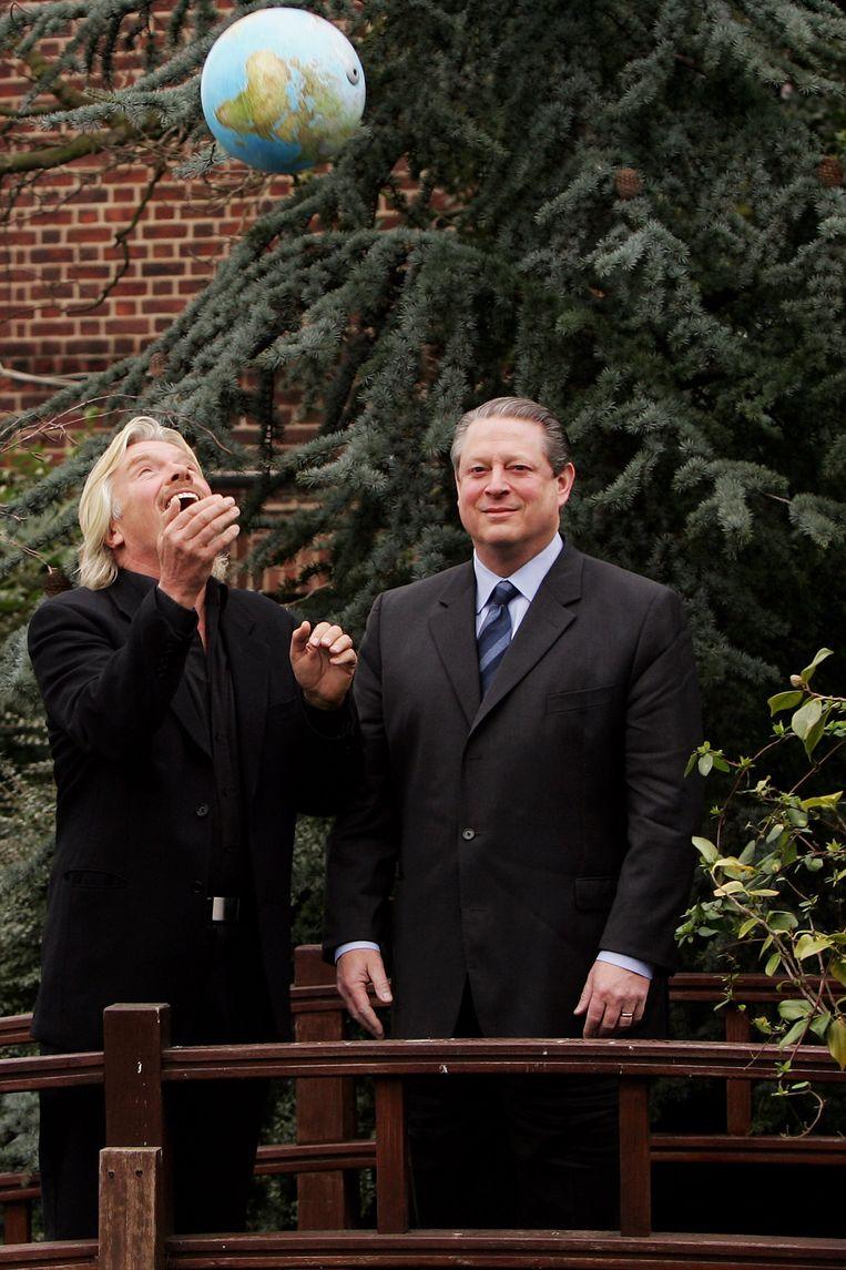 Richard Branson gooit een globe de lucht in bij de presentatie van de Virgin Earth Challenge in Londen, februari 2007, met naast hem Al Gore. Beeld Getty Images