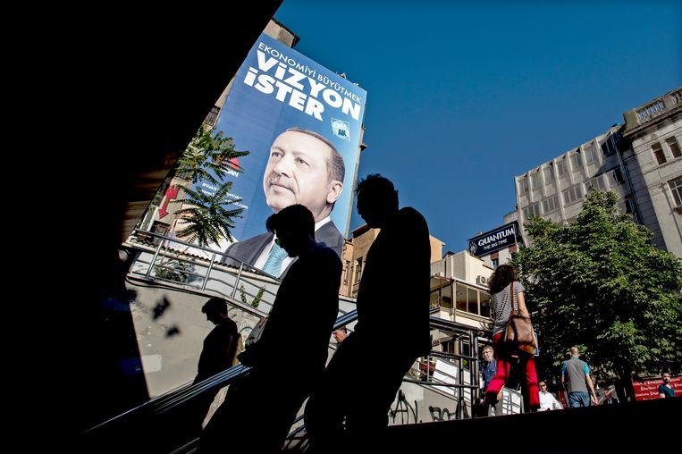 Voorbijgangers lopen langs een affiche van Turks president Erdogan. Beeld EPA