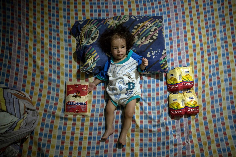 Een éénjarig meisje in Caracas, met naast zich een paar zakken voedingsmiddelen. Eten is voor veel Venezolanen momenteel een nauwelijks betaalbare luxe.