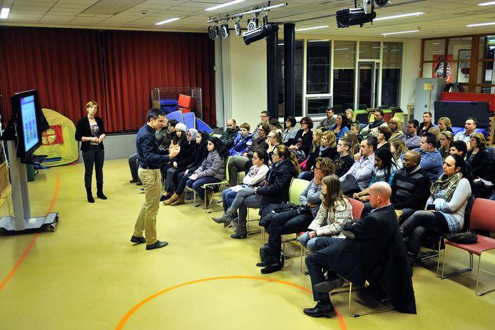 Herman Verschuren van het Markland College Zevenbergen spreekt kinderen uit groep 8 en hun ouders toe tijdens de scholenmarkt 2014 in de Arenbergschool in Zevenbergen.
