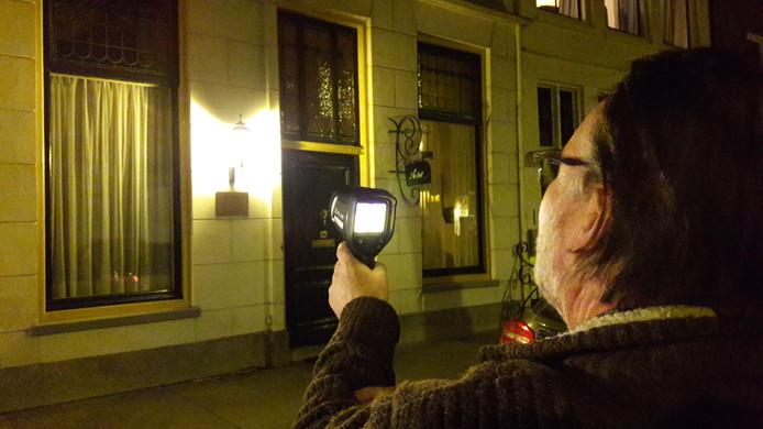 Wim van Rooij richt de warmtebeeldcamera op een woning aan de Gasthuisstraat in Zaltbommel.