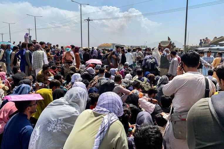 Mensen verzamelen aan de luchthaven van Kaboel in de hoop met een evacuatievliegtuig het land te kunnen verlaten. Beeld AFP
