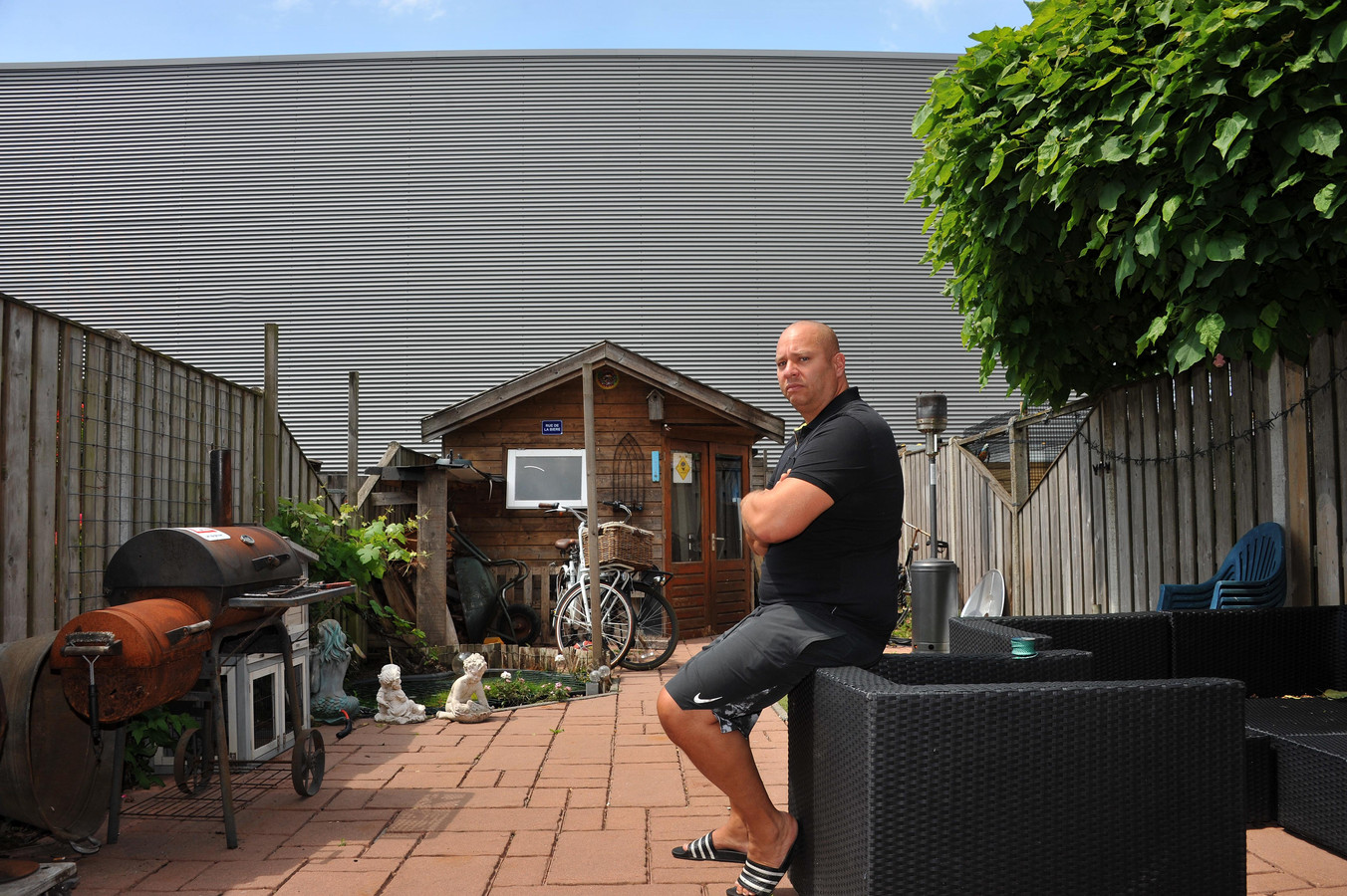 Edwin de Visser uit Rijksstraatweg kijkt tegen de stalen wand van de bedrijfshal aan die tegen zijn achtertuin is geplaatst. Nu verdwijnt ook zijn zij-uitzicht.