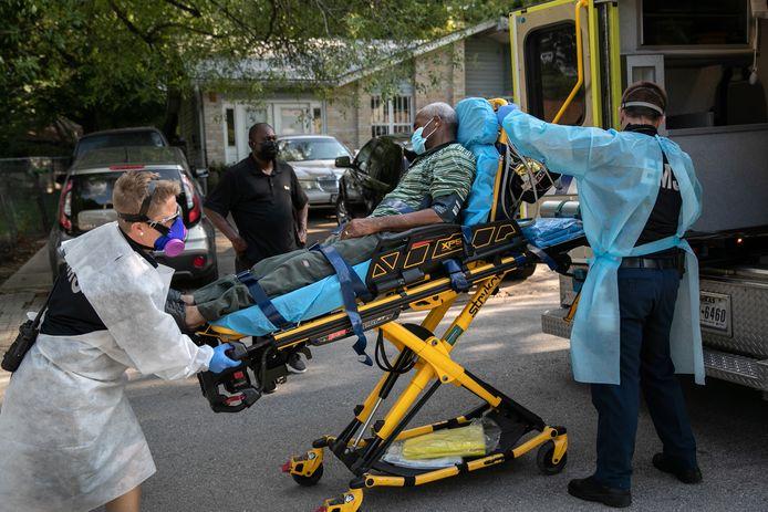 Een met het coronavirus besmette man wordt in Austin, Texas in een ambulance getild. Archiefbeeld.