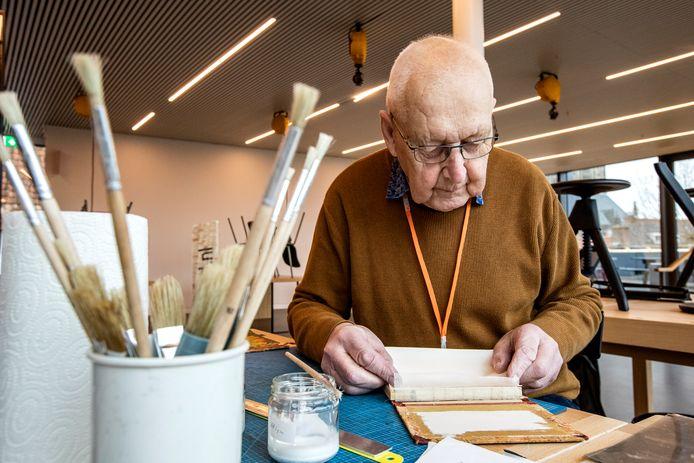 Jan Boersma plakt de rug van een oud kinderboek.