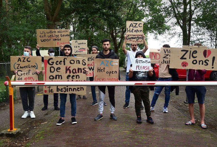 Voor de poort van het azc in Zweeloo protesteren asielzoekers tegen de ongelijke behandeling van asielaanvragen. Beeld Marcel van den Bergh / de Volkskrant