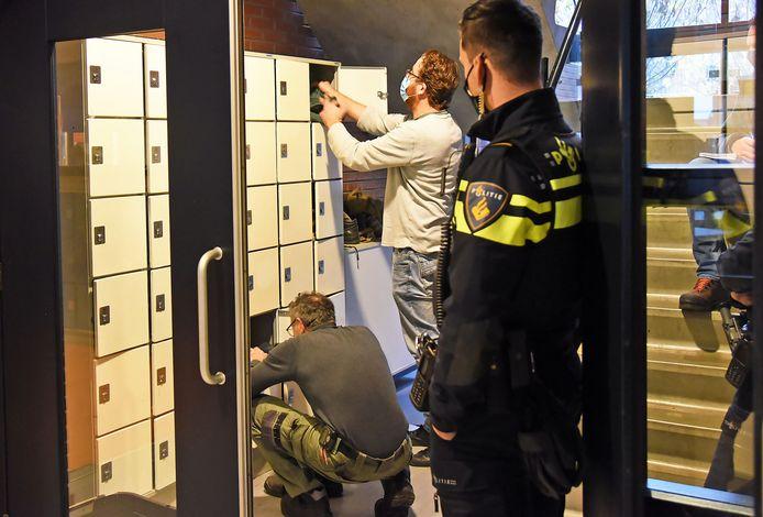 Onder toeziend oog van de politie worden op Praktijkschool De Sprong de kluisjes doorzocht door docenten Johan le Feber (knielend) en Peter Quaak.