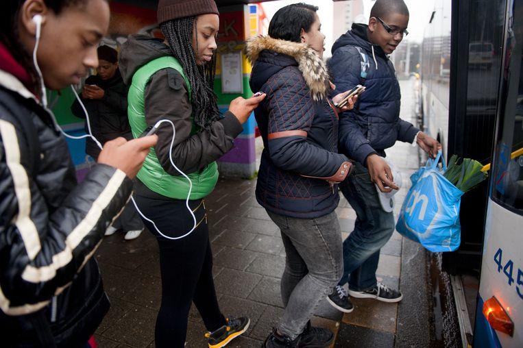 Jongeren in Amsterdam-Noord bij de bushalte. De smartphone is uit hun leven niet meer weg te denken, dus hoe goedkoper hoe beter. Beeld An-Sofie Kesteleyn