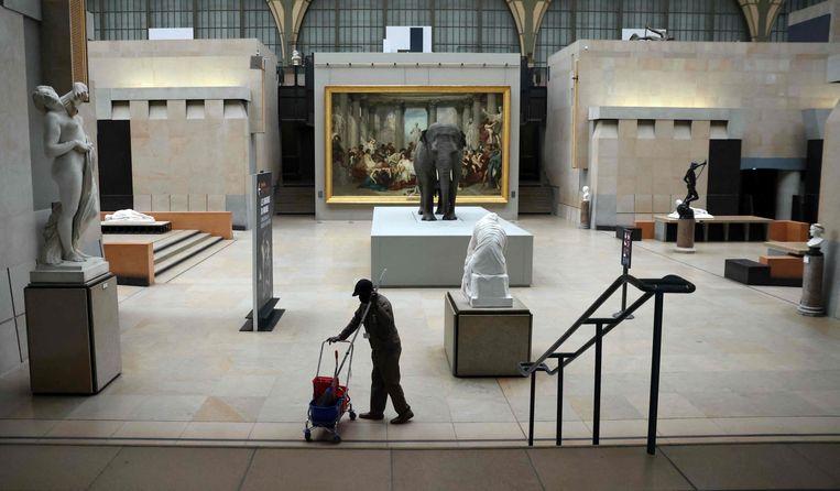 Een medewerker van het Parijse Musée d'Orsay treft voorbereidingen voor de heropening van het museum. Morgen openen culturele instellingen in heel Frankrijk hun deuren. Dit markeert een nieuwe stap in de beëindiging van de derde nationale coronalockdown. Beeld AFP