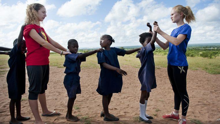 Sarah (18, links) uit Luik en de 19-jarige Synne uit Noorwegen (rechts) geven gymnastiekles aan basisschoolkinderen in Livingstone, Zambia. Beeld An-Sofie Kesteleyn