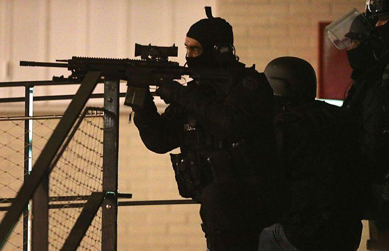 Franse agenten houden het gebouw in Reims onder schot dat doorzocht wordt Beeld afp