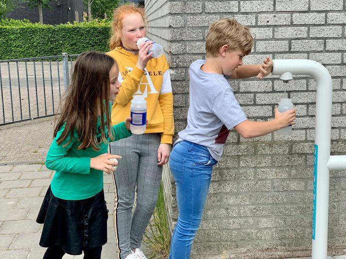 Leerlingen vullen hun bidon met vers water uit het nieuwe watertappunt.