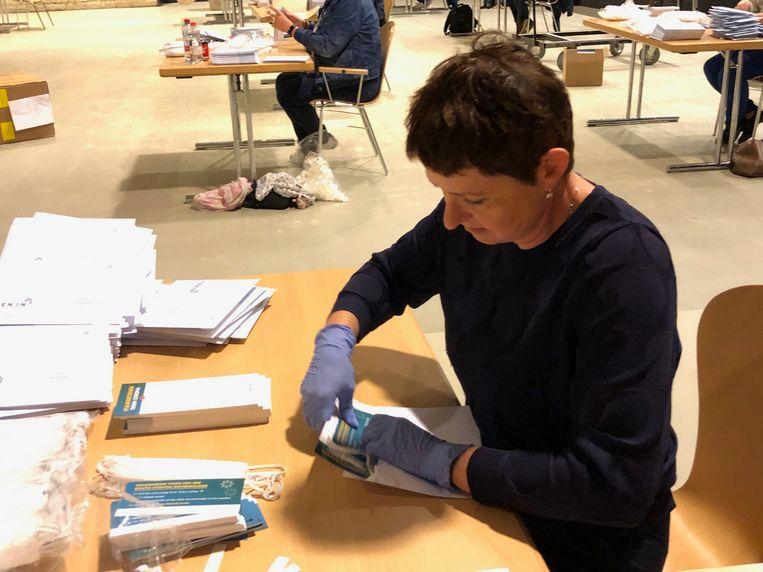 Medewerkers maken de mondmaskers klaar voor verzending