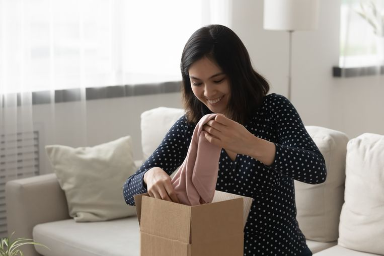 Happy interested asian female customer receive unpack parcel box ordered at fashion boutique online store. Smiling young vietnamese woman get stylish clothing as present gift by mail courier delivery Beeld Getty Images/iStockphoto