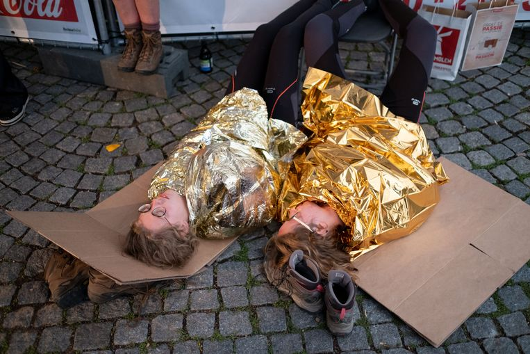 Twee uitgeputte wandelaars liggen onder een thermisch deken aan de aankomst.