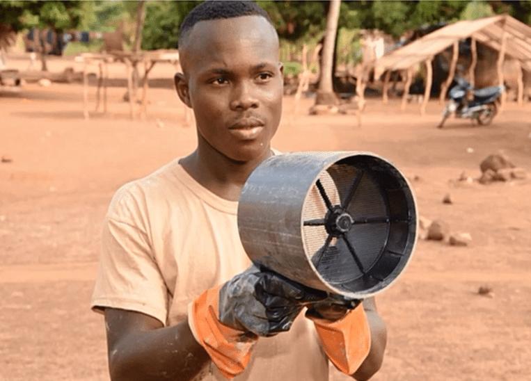 Een man in Ivoorkust demonstreert de ventilatiebuizen. Muggen vliegen er doorheen omdat ze de geur van mensen ruiken, maar komen niet ver omdat er roosters met gif in de buis zitten. Beeld In2Care