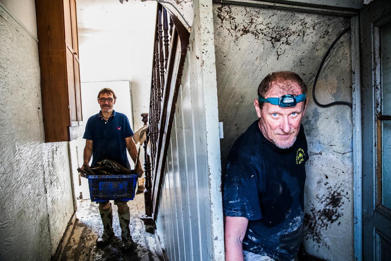 Roger Kieronski (rechts) is uit Vlaanderen komen rijden om te zien of hij kon helpen. Hij schept nu puin uit het huis van Didier Grün. Beeld Aurélie Geurts