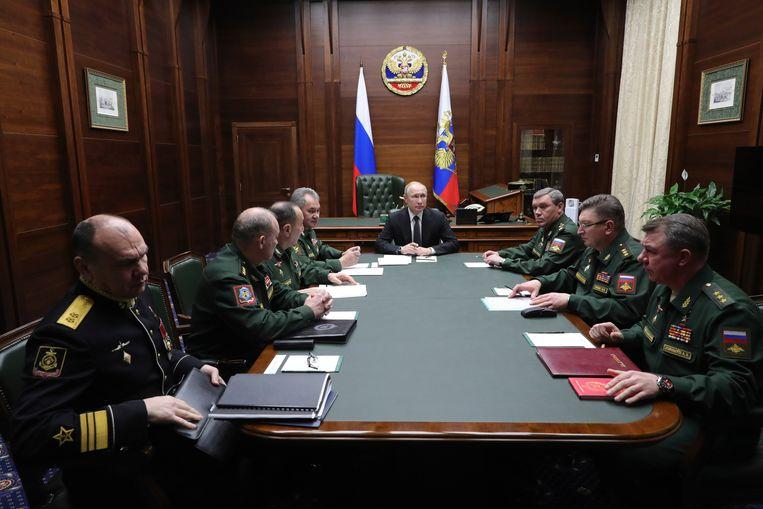 De Russische president Vladimir Poetin (midden) tijdens een bespreking met de Russische militaire leiders dinsdag in het nationale defensie-controlecentrum in Moskou. Beeld AP
