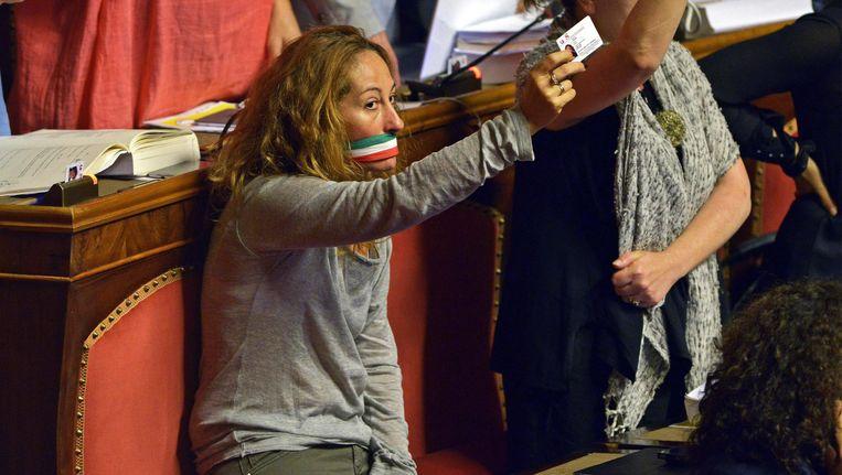 Senator Paola Taverman van de 5-Sterrenbeweging van Beppe Grillo heeft uit protest haar eigen mond gesnoerd. Na een tumultueuze sessie stemde de Italiaanse senaat vanavond voor zijn eigen afschaffing. Beeld EPA