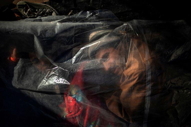 Een vluchteling onder een zeil ontwaakt in Tijuana. Beeld REUTERS