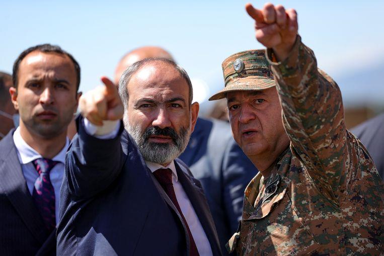 De interim-premier van Armenië, Nikol Pashinyan (midden), wordt bijgepraat door generaal Arayik Harutyunyan over het gebied waar mijnen zouden liggen. Beeld AP