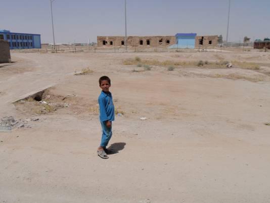 Een Afghaans jongetje dat bij militairen om water komt vragen