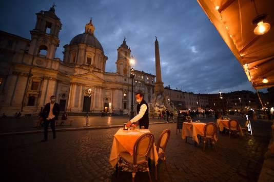 Een ober ruimt een tafel af op het Piazza Navona in Rome.
