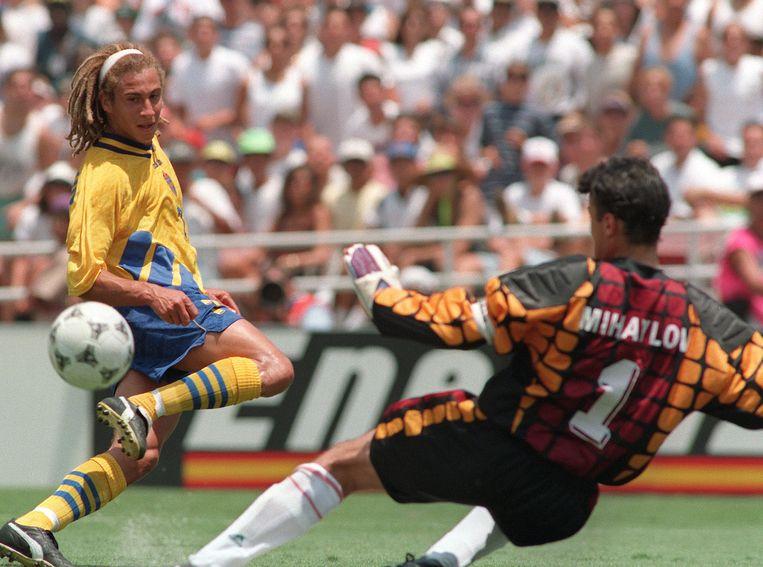 De Zweedse voetballer Henrik Larsson schopt de bal langst de Bulgaarse keeper Borislav Mihaylov. Zweden won de wedstrijd met 4-0. Beeld AFP