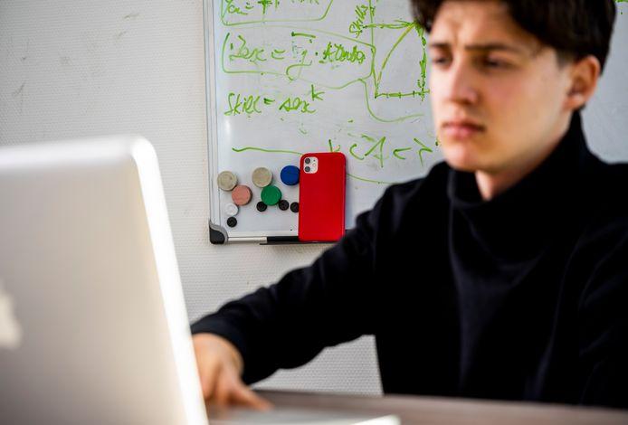 Twee camera's houden een student in de gaten: de webcam én de mobiele telefoon.