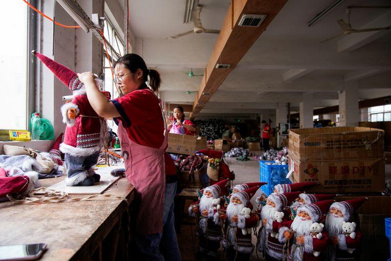 Een werknemer van een speelgoedfabriek zet een kerstman in elkaar in Yiwu, in de Chinese provincie Zhejiang. Beeld REUTERS