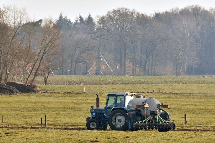 Ter illustratie: een boer die mest uitrijdt over het land.
