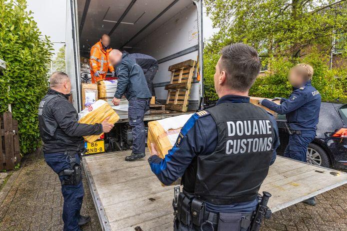 De douanebeambten, van wie enkelen bewapend, voeren de inbeslaggenomen tabaksspullen af.