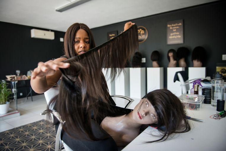 Sisi Nxumalo werkt aan een pruik in haar salon in Johannesburg. Beeld Bram Lammers