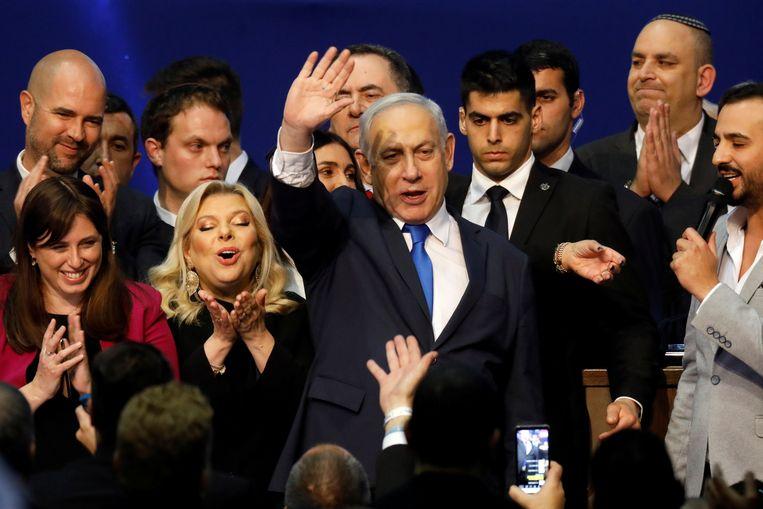 Premier Benjamin Netanyahu van Israël viert de exitpolls met aanhangers tijdens de verkiezingsnacht. Beeld REUTERS