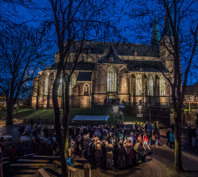 Dickens Festijn 2017 in Deventer. Zingen rond een lantaarnpaal, met de verlichte kerk op de achtergrond. Foto Rob Voss