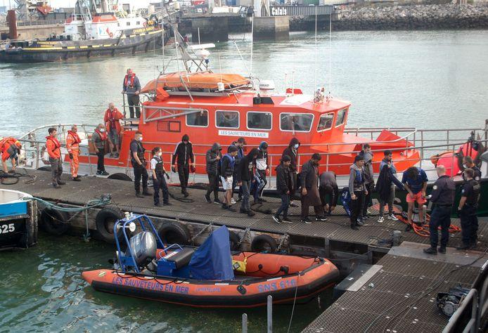 Iraakse, Iraanse en Afghaanse migranten stappen uit nadat ze gered werden door een schip van de Franse kustwacht.