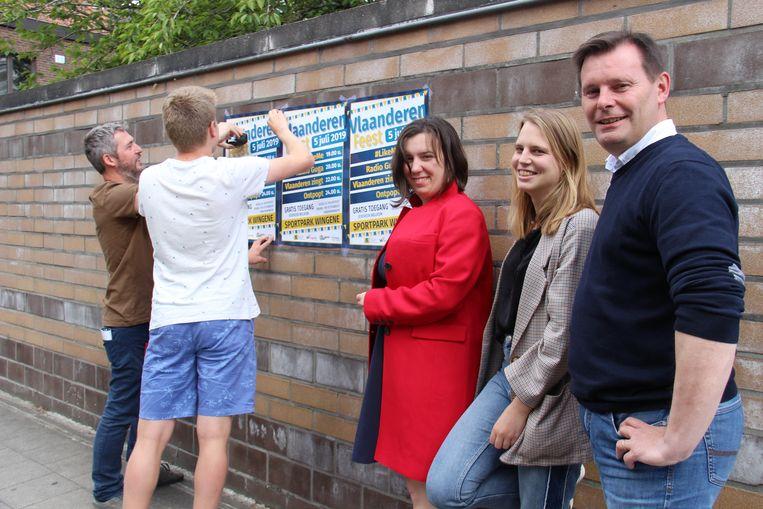 Schepen van Cultuur Lieven Huys en enkele medewerkers van de Cultuurdienst hangen de eerste affiches voor Vlaanderen Feest op