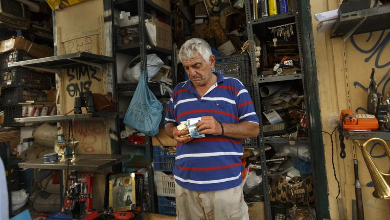 Een Griekse marktkoopman telt zijn geld. Beeld ap