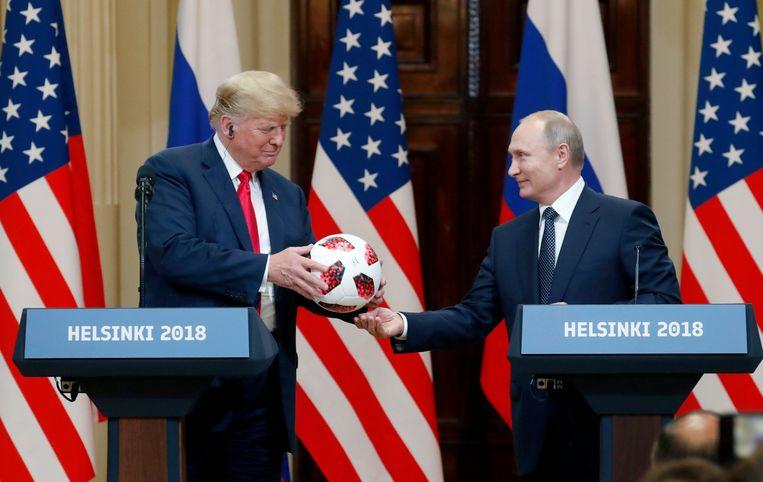 Poetin overhandigt Trump de zwart-rood geblokte WK-bal na afloop van hun privéontmoeting in Helsinki op 16 juli.  Beeld Anatoly Maltsev / EPA