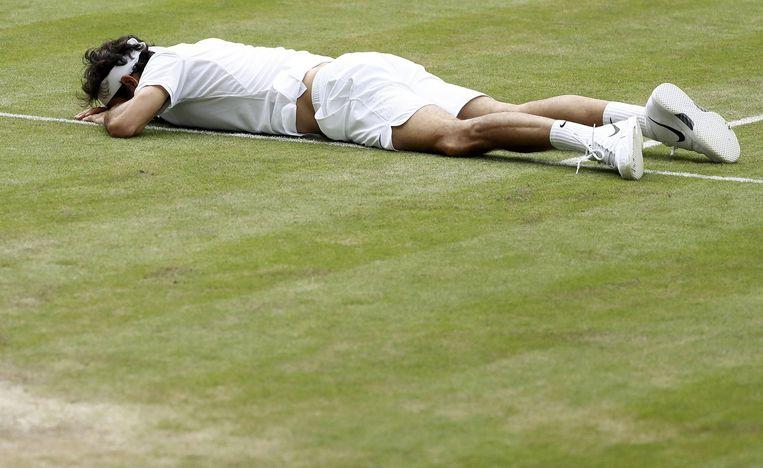 Federer ligt op de baan na een struikelpartij. Beeld reuters