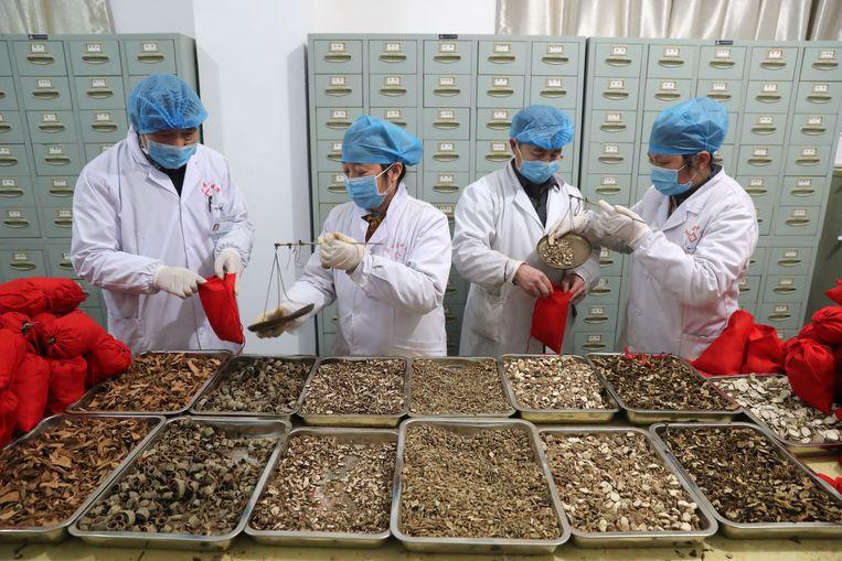 Medewerkers van een ziekenhuis voor traditionele Chinese geneeskunde bereiden zakjes kruiden voor patiënten met het nieuwe coronavirus. Beeld Reuters