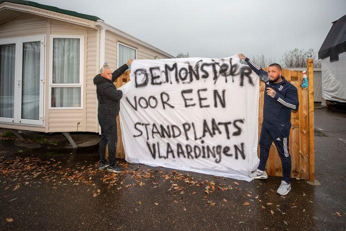 Piet van Schaften (links) en zoon Danny bij de illegaal geplaatste stacaravan. Beiden vinden dat de eerder door Vlaardingen opgeheven standplaatsen terug moeten keren, omdat daar behoefte aan is.