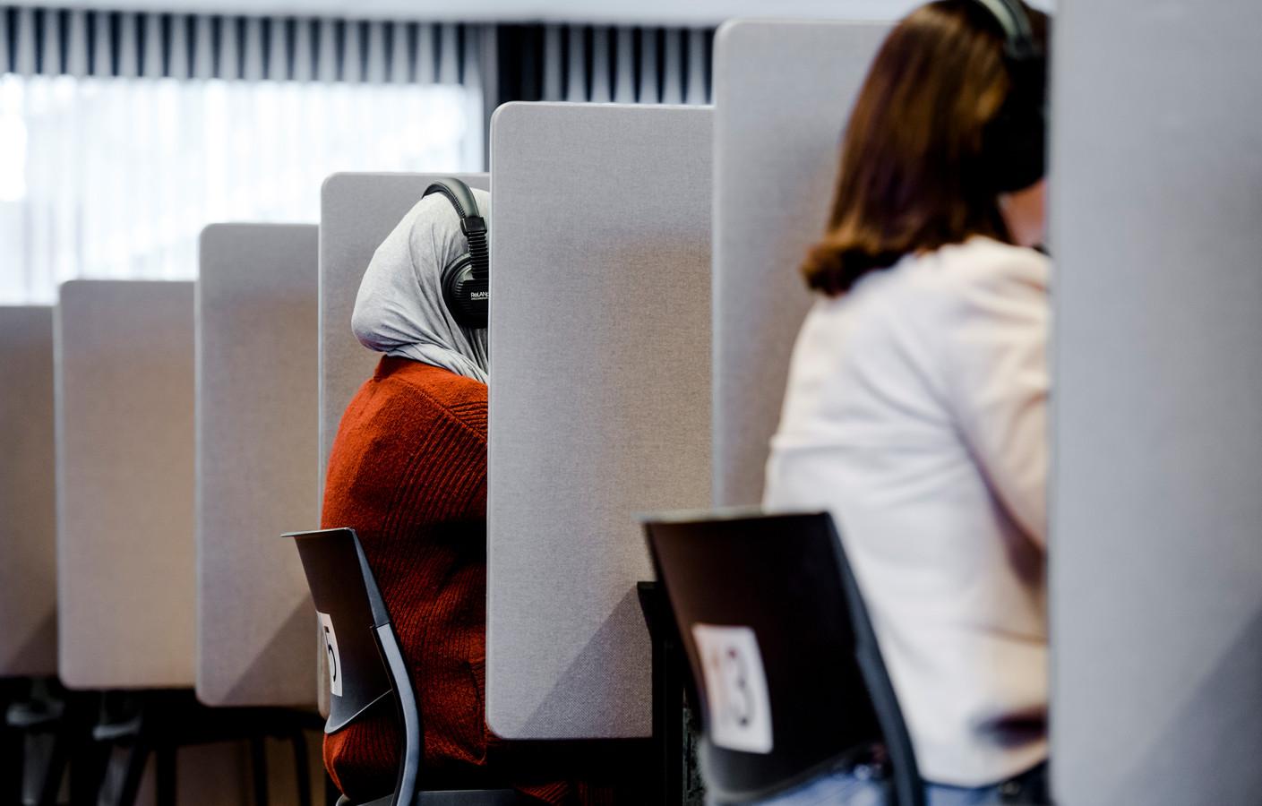 Twee buitenlandse vrouwen doen het inburgeringsexamen op een toetslocatie van de Dienst Uitvoering Onderwijs (DUO). Beeld ter illustratie.