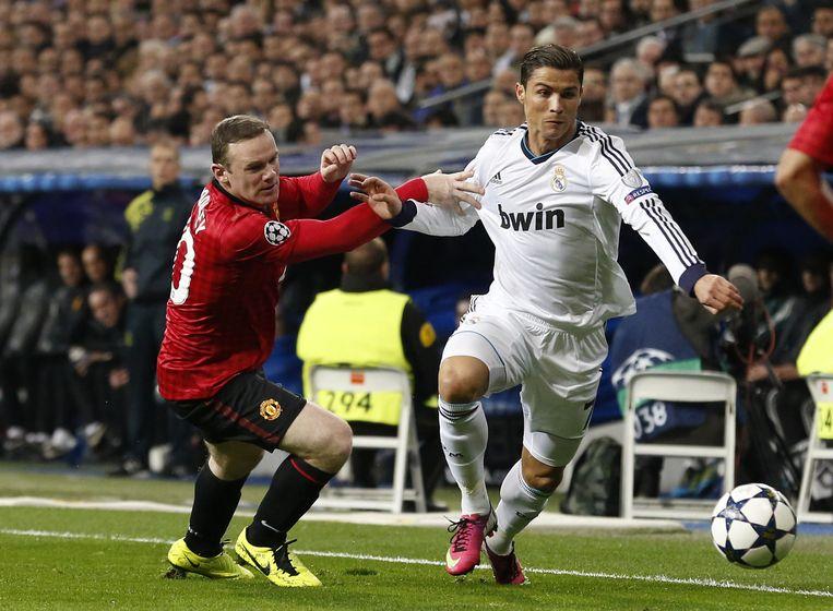 Cristiano Ronaldo (r) van Real Madrid in duel met Wayne Rooney van Manchester United tijdens de eerste halvefinalewedstrijd in de Champions League. Beeld AFP