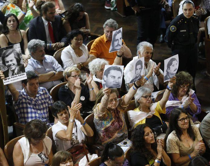 Leden van mensenrechtenorganisaties houden foto's van de slachtoffers omhoog tijdens de rechtszaak over de martelingen in La Plata.