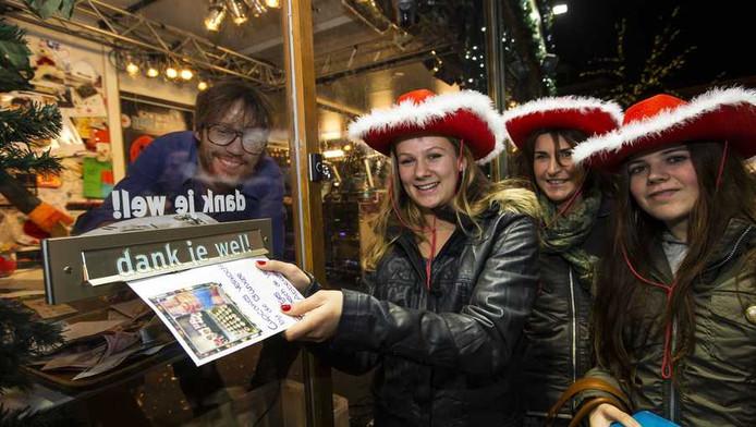 Drie meisjes posten hun gift door de brievenbus in het Glazen Huis bij dj Giel Beelen.