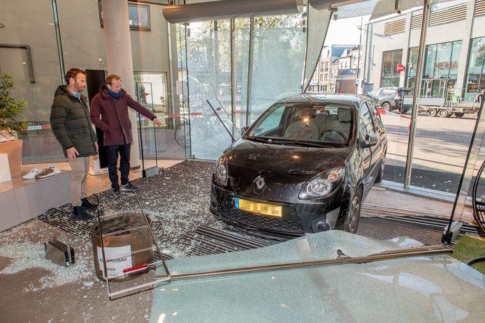 Eigenaren Max (l) en Bram van Blijdesteijn bij de auto die vorige week de pui van hun modezaak ramde.