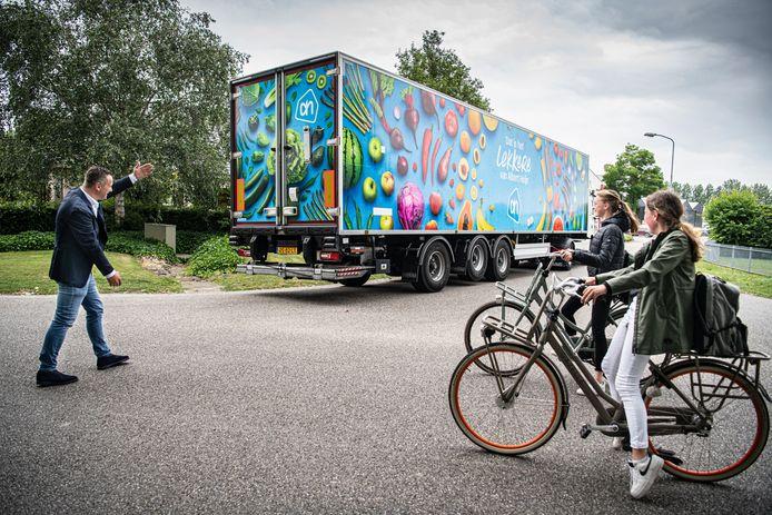 Barry Moors regelt het verkeer terwijl een vrachtwagen achteruit vanaf een doodlopende weg op bedrijventerrein Breekwagen de Grotestraat insteekt. Scholieren met fiets blijven zo lang wachten.